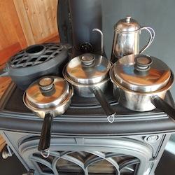 薪ストーブの天板に並ぶ鍋たち